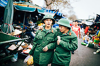 Two young men in army uniforms walk through the market in Hue, Vietnam.