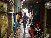 18 SEPTEMBER 2015 - BANGKOK, THAILAND: A woman finishes doing her dishes in the neighborhood near Wat Kalayanamit. Like her neighbors, she is being evicted from her home. Fiftyfour homes around Wat Kalayanamit, a historic Buddhist temple on the Chao Phraya River in the Thonburi section of Bangkok are being razed and the residents evicted to make way for new development at the temple. The abbot of the temple said he was evicting the residents, who have lived on the temple grounds for generations, because their homes are unsafe and because he wants to improve the temple grounds. The evictions are a part of a Bangkok trend, especially along the Chao Phraya River and BTS light rail lines. Low income people are being evicted from their long time homes to make way for urban renewal.             PHOTO BY JACK KURTZ