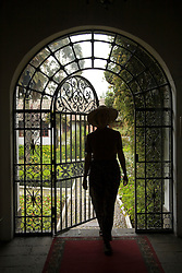 South America, Ecuador, Lasso, woman in arch with wrought-iron door to garden, Hacienda La Cienega  MR
