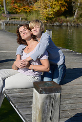 Mother and son sitting and embracing each other on boardwalk, Bavaria, Germany