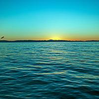 The sun sets behind Santa Catalina Island in the Pacific Ocean near Los Angeles, California.