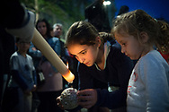 """Children attending the long processions, waiting for hours for the whole thing to pass, spend their time collecting the wax dripping from the candles carried by the """"penitentes"""". Granada, Spain"""