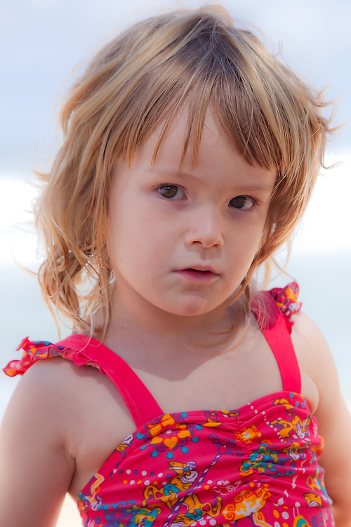 A small girl looks inquisitively at the camera