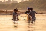 Group of men net fishing in a river in Thailand at sunset