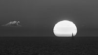 Silhouette of a Sailboat Passing in Front of the Sun at Sunset from the Deck of the MV Explorer. Crossing the Baltic Sea from Stockholm to Copenhagen. Image taken with a Nikon D4 camera and 80-400 mm VRII lens (ISO 400, 400 mm, f/11, 1/500 sec).