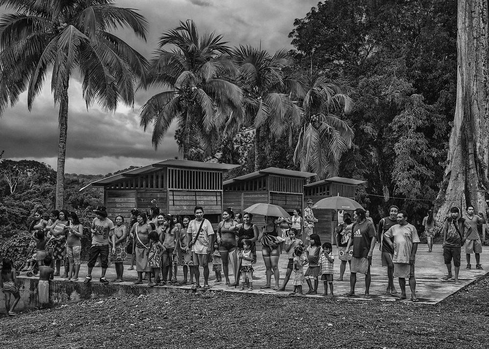 """Camopi, Guyane, 2015.<br /> <br /> Depuis cette photo, pour la troisième fois en dix-huit mois les électeurs de Camopi sont retournés aux urnes le 20 septembre 2015 pour élire leur maire. <br /> <br /> Après trois mandats à la tête de la commune, Joseph Chanel est battu en 2008 par René Monerville. De nouveau battu, en mars 2014 face à René Monerville, Joseph Chanel dépose alors un recours pour des irrégularités constatées dans le bureau de Trois-Sauts, à plusieurs heures de pirogues. Après avoir obtenu gain de cause et fait annuler l'élection, il remporte le scrutin organisé en novembre 2014. En juin 2015, le Conseil d'Etat annule ce scrutin et donne raison René Monnerville : le délai de convocation des électeurs du bureau de Trois-Sauts n'a pas été respecté d'autant qu'il existe """"des difficultés de diffusion de l'information liées aux caractéristiques géographiques de cette commune ainsi qu'aux problèmes de circulation aggravée par le bas niveau du fleuve Oyapock"""". Cela est de nature à """"altérer la sincérité du scrutin"""".<br /> Entretemps, Joseph Chanel a pu faire voter par son conseil municipal l'adhésion de sa commune à la charte du Parc amazonien de Guyane qui avait été unanimement rejetée par l'équipe de son prédécesseur.<br /> <br /> Joseph Channel remporte finalement l'élection à la mairie de Camopi le dimanche 20 septembre 2015 avec seulement deux voix d'écart contre Laurent Yawalou, tête de liste de la nouvelle équipe Monerville. <br /> Un nouveau recours a été déposé pour faire annuler l'élection : de jeunes majeurs de Camopi ne seraient pas inscrits sur les listes électorales, l'âge déclaré sur leurs papiers d'identité serait inexacte. <br /> <br /> L'isolement de Camopi des centres administratifs du département semble questionner les limites du système."""