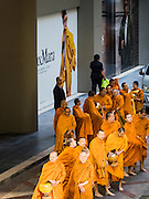 "29 NOVEMBER 2016 - BANGKOK, THAILAND: Buddhist monks walk past a billboard at the Gaysorn Shopping Center in Bangkok before a special ""tak bat"" or merit making ceremony. The tak bat was to honor Bhumibol Adulyadej, the Late King of Thailand. Food and other goods were given to the monks, who in turn gave the items to charities that will distribute them to Bangkok's poor. More than 100 Buddhist monks participated in the merit making ceremony. The ceremony was organized by the merchants in the Ratchaprasong Intersection, which includes some of Bangkok's most upscale shopping centers.      PHOTO BY JACK KURTZ"