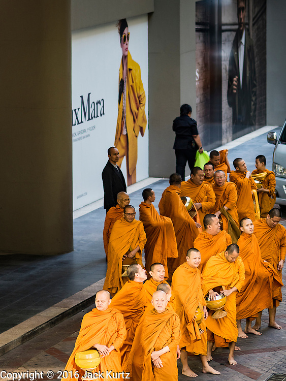 """29 NOVEMBER 2016 - BANGKOK, THAILAND: Buddhist monks walk past a billboard at the Gaysorn Shopping Center in Bangkok before a special """"tak bat"""" or merit making ceremony. The tak bat was to honor Bhumibol Adulyadej, the Late King of Thailand. Food and other goods were given to the monks, who in turn gave the items to charities that will distribute them to Bangkok's poor. More than 100 Buddhist monks participated in the merit making ceremony. The ceremony was organized by the merchants in the Ratchaprasong Intersection, which includes some of Bangkok's most upscale shopping centers.      PHOTO BY JACK KURTZ"""