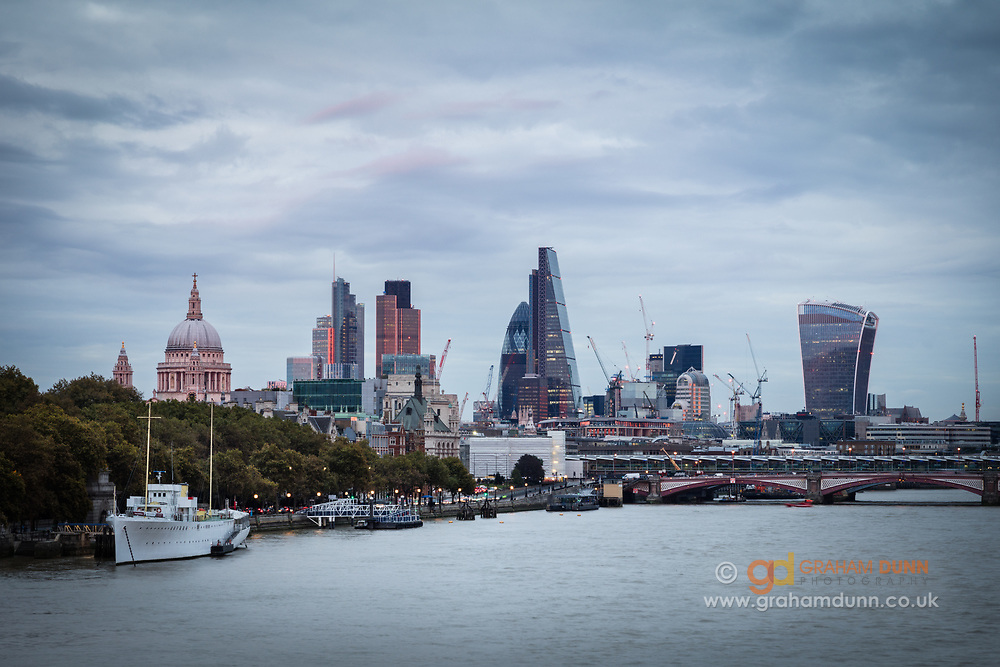 The last moments of orange/red light from the setting sun casts a soft glow over the London skyline, as captured from Waterloo Bridge. Numerous famous landmarks are seen here, framed by St Paul's Cathedral and The Walkie Talkie. A classic cityscape of our capital city - London, England, UK.
