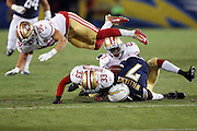 San Francisco 49ers linebacker Shayne Skov (56) flies over the pile after San Diego Chargers wide receiver Dom Williams (7) is tackled by San Francisco 49ers cornerback Will Redmond (23) on a second quarter pass play plus a personal foul penalty for a late hit by San Francisco 49ers cornerback Rashard Robinson (33) that gives the Chargers a first down and goal to go inside the ten yard line during the 2016 NFL preseason football game against the San Francisco 49ers on Thursday, Sept. 1, 2016 in San Diego. The 49ers won the game 31-21. (©Paul Anthony Spinelli)