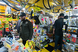 Andy Carter buys goodies during a visit to Z-Father Bōsōzoku motorcycle shop after Mooneyes. Tokyo, Japan. December 8, 2015.  Photography ©2015 Michael Lichter.