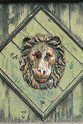 Faded green wooden door with lion relief and rhombus, Trieste, Italy