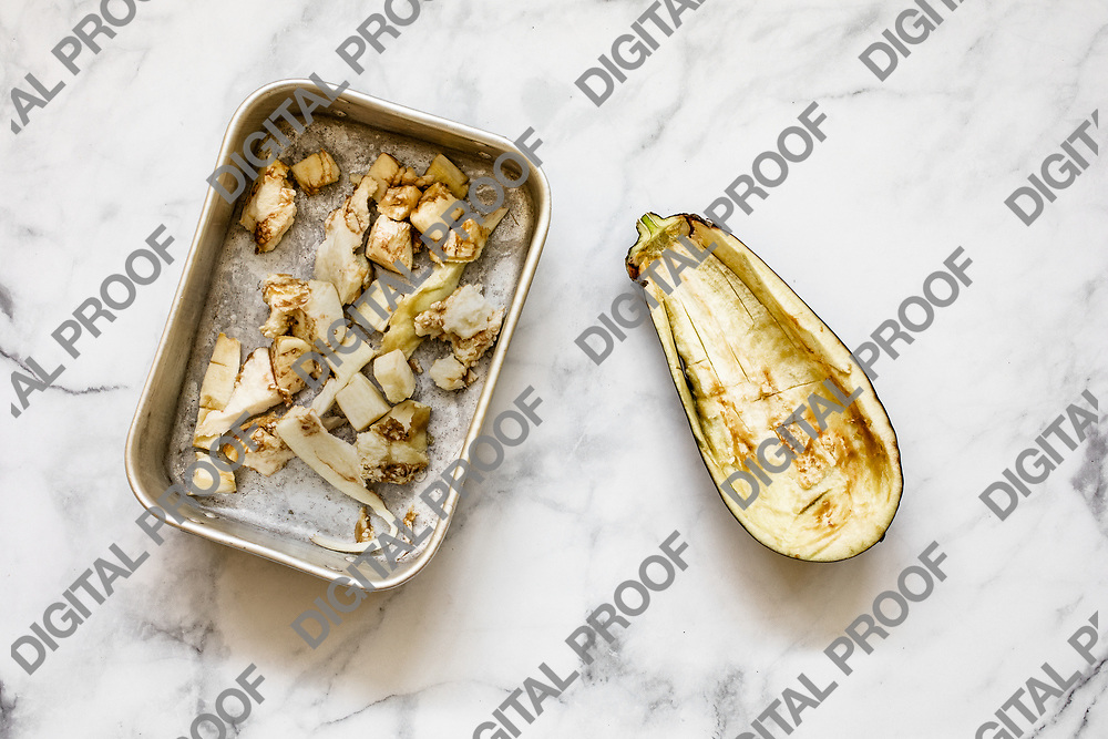 Half aubergine in dices placed in a metal tray with flatlay look light theme