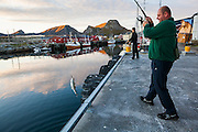 An off-duty fish factory employee (who came from Poland looking for work) hooks a fish at the commercial port in Sorland, Vaeroy Island, Lofoten Islands, Norway.