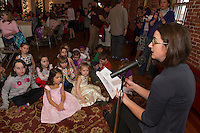 """Jocelyn Sprague and Gracie Dube listen as Author Jennifer Carson reads a chapter from """"Hapenny Magick"""" during Lakes Region Community Services sponsored Children's Authors Tea at the Belknap Mill Tuesday evening.   (Karen Bobotas/for the Laconia Daily Sun)"""