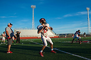 Iraan High School quarterback Clayton Kent #11 drops back to pass during practice while head coach Mark Kirchhoff looks on in Iraan, Texas on December 13, 2016. (Cooper Neill for The New York Times)