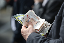 © Licensed to London News Pictures. 09/04/2016. Liverpool, UK. A punter eyes up the odds with money in hand on Grand National day of the Grand National 2016 at Aintree Racecourse near Liverpool. The race, which was first run in 1839, is the most valuable jump race in Europe. Photo credit : Ian Hinchliffe/LNP