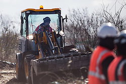 Licensed to London News Pictures. 03/03/2016. Calais, France. A contractor moves a digger in to clear the debris from the demolition area. French authorities are clearing the southern half of the Calais 'Jungle' camp, which charities estimate to contain 3,500 people. Photo credit : Rob Pinney/LNP