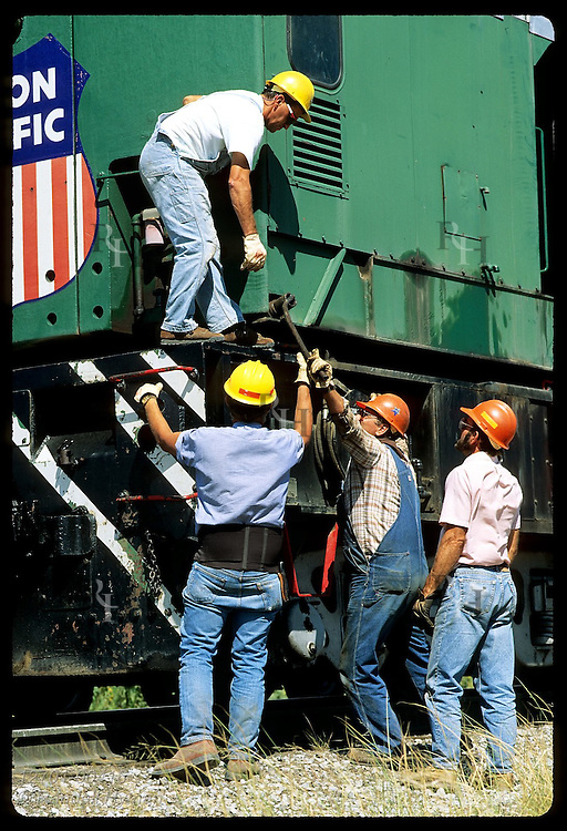 Men work to crank wrench on crane car in Union Pacific's Bailey Yard at North Platte. Nebraska
