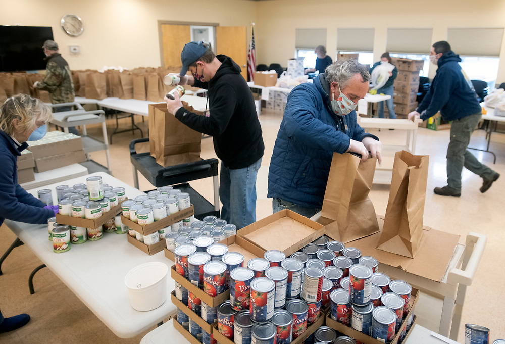 HYANNIS - Volunteers from the town's golf courses fills bags of groceries for seniors at the Adult Community Center on Friday, April 3, 2020. The crew was tasked with putting together 240 bags of food to be delivered to seniors.