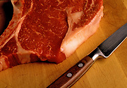 Close up photo of a raw steak on a butcher block with a knife next to it