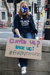 A NHS worker holds a sign calling for fair pay for nurses at a protest rally opposite Downing Street as part of a national day of action to mark the 73rd birthday of the National Health Service on 3rd July 2021 in London, United Kingdom. As well as fair pay for NHS workers, the protesters called for better funding of the NHS and for an end to privatisation measures affecting the NHS.