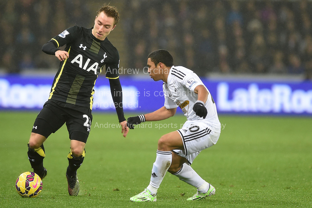 Christian Eriksen of Tottenham (l) is challenged by Jefferson Montero of Swansea city.  Barclays Premier League match, Swansea city v Tottenham Hotspur at the Liberty Stadium in Swansea, South Wales on Sunday 14th December 2014<br /> pic by Andrew Orchard, Andrew Orchard sports photography.