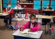 First grader Sophia Frazier does her work in a plastic barricade during class at Twin Rivers Elementary School on Monday, March 8, 2021. Only the students near the teacher's desk seem to have dividers.