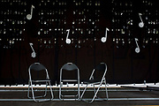 Three seats awaiting musicians before a local village concert at Wells-next-the-Sea in Nofolk. Quavers and a pattern of other musical notations appear on the black background while the fold-up chairs are untidily vacant.