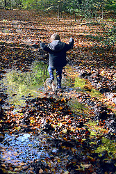 © Licensed to London News Pictures. 04/11/2013. Burnham, UK A young boy jumps in muddy puddles. Autumn sunshine through the trees at Burnham Beeches, South Buckinghamshire on MONDAY 4TH NOVEMBER. The beeches covering 220 hectares is primarily noted for its ancient beech and oak pollards. Photo credit : Stephen Simpson/LNP