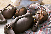 Two naked severely malnourished children, covered with flies, lay resting on a blanket during therapeutic feeding from Medecins sans Frontieres (MSF). Ajiep, Bahr el Ghazal, Sudan. The famine in Sudan in 1998 was a humanitarian disaster caused mainly by human rights abuses, as well as drought and the failure of the international community to react to the famine risk with adequate speed. The worst affected area was Bahr El Ghazal in southwestern Sudan. In this region over 70,000 people died during the famine.