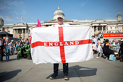 © Licensed to London News Pictures. 21/04/2018. London, UK. A man with a large England flag attends the 'Feast of St George' event in Trafalgar Square, to celebrate the Patron Saint of England. St George's Day is on 23 April. Photo credit : Tom Nicholson/LNP