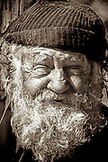 Portrait of a weathered old sailor with a white beard.