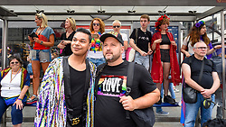 © Licensed to London News Pictures. 06/07/2019. LONDON, UK.  People watch the parade from a bus stop vantage point. Tens of thousands of visitors, many wearing eye-catching costumes, gather to watch and take part in the annual Pride in London Parade, the largest celebration of the LGBT+ community in the UK.  This year's event also celebrates 50 years since the birth of the modern LGBT+ rights movement. Photo credit: Stephen Chung/LNP