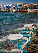Mykonos Little Venice - rows of fishing houses line the waterfront with their balconies hanging over the sea. The first of these was constructed in the mid-18th century. They originally belonged to rich merchants or captains and the little basement doors that provided direct access to the sea and underground storage areas led people to believe that the owners were secretly pirates. Some of the houses have now been converted into bars and cafes and little shops and galleries. Little Venice is considered one of the most romantic spots on the island and many people gather there to watch the sunset. The area attracts many artists who come to paint the picturesque coastline.
