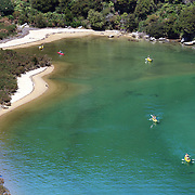 Kayakers venture down crystal clear waters of a sheltered lagoon in the Abel Tasman National Park., South Island, New Zealand, The Abel Tasman National Park at the top of the South Island was established in 1942. it is renowned for its golden beaches, sculptured granite cliffs, native wildlife encounters and beautiful scenery..A number of kayaking companies run guided tours from Marahau, Kaiteriteri and Golden Bay. Abel Tasman National Park, South Island, New Zealand. 5th.February 2011, Photo Tim Clayton.