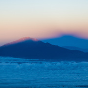 Mt Kilimanjaro casts a well-defined shadow over Mt Meru just after dawn as seen from part way up the Western Breach (approx 17,000 feet) on Kilimanjaro.