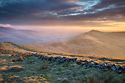A colourful sunrise view from Mam Tor, looking along the Great Ridge to Lose Hill.  A crumbling drystone wall forms the foreground, with the Edale and Hope Valleys on either side of the Ridge. A classic Peak District scene, Derbyshire, England, UK.