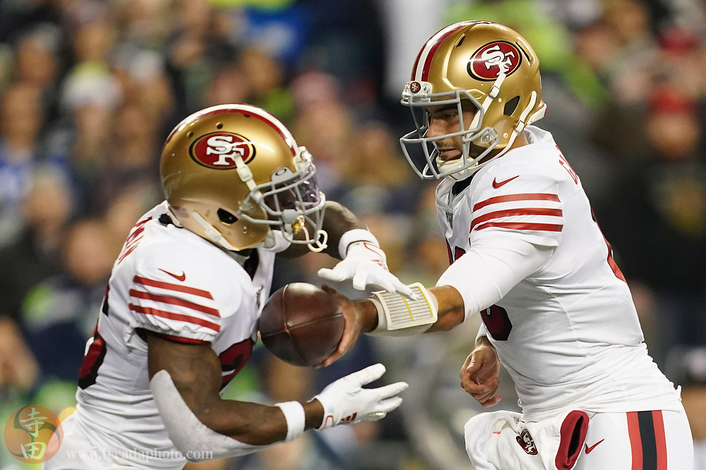 December 29, 2019; Seattle, Washington, USA; San Francisco 49ers quarterback Jimmy Garoppolo (10) hands off to running back Tevin Coleman (26) during the first quarter against the Seattle Seahawks at CenturyLink Field.