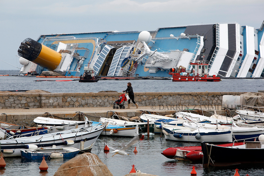 A woman with a child in a pushchair walks along a jetty near the capsized cruise liner Costa Concordia off the west coast of Italy at Giglio island February 2, 2012.    ..REUTERS/Darrin Zammit Lupi (ITALY)