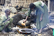 Africa, Ethiopia, Lalibela, Woman cooking Injera (pancake like bread from teff flour) on a mogogo over a fire