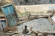 A laborer breaks rocks for use in construction in the village of Nesang in Himachal Pradesh, India. People breaking rocks earn a few dollars per day.