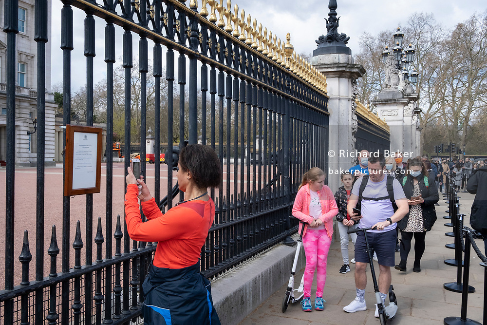 Following the announcement of the death at age 99 of Prince Phillip, the Duke of Edinburgh, consort to Queen Elizabeth II, the public file past the official notice which has been attached to the railings outside Buckingham Palace, on 9th April 2021, in London, Emgland.