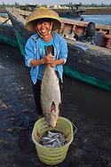 Sea bass and happy fisherwoman holding it, Shi Ma Jiao harbour, Guangdong province, China
