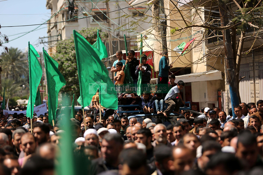 April 14, 2017 - Khan Younis, Gaza Strip, Palestinian Territory - Hamas supporters hold crossed posters depicting Palestinian President Mahmoud Abbas and Palestinian Prime Minister Rami Hamdallah during a protest against them in Khan Younis in the southern Gaza Strip April 14, 2017  (Credit Image: © Ashraf Amra/APA Images via ZUMA Wire)