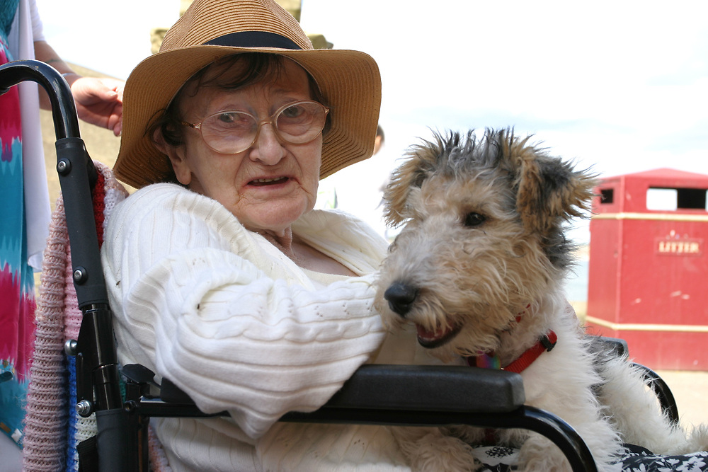 Elderly disabled women in wheel chair with pet dog.