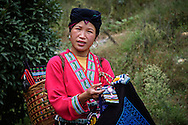 Tribal Zhuang woman selling handcrafted articles.