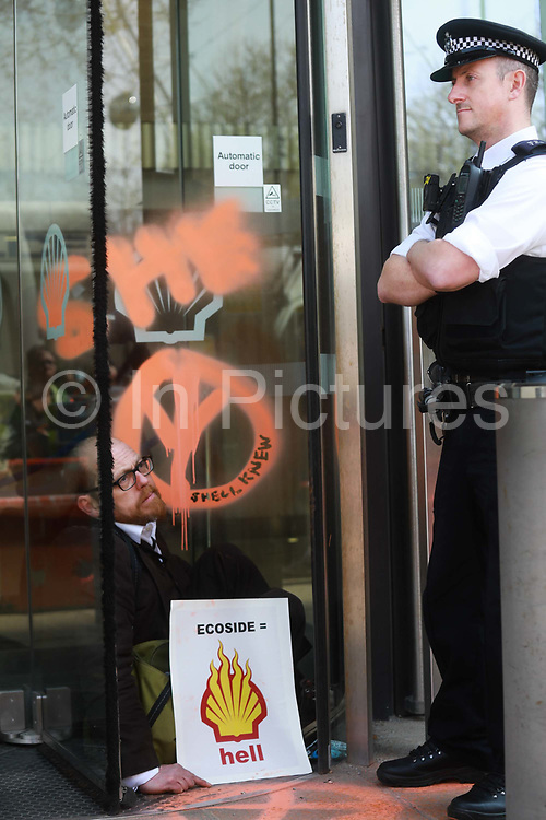 Three activists super glued themselves to the glass doors of the Shell Building and two scaled the glass awning in protest against the oil companys continued exploitation of fossil fuels, 15th April 2019, Central London, United Kingdom. A number of arrests were made. The environmental protest group Extinction Rebellion has called for civil disobedience and peaceful protest to force the British government to take drastic action on climate change. The group wants the governenmet to tell the truth and admit that the impact of climate change is much more severe than they say and that action to mitigate catastrophic climate change is urgent.