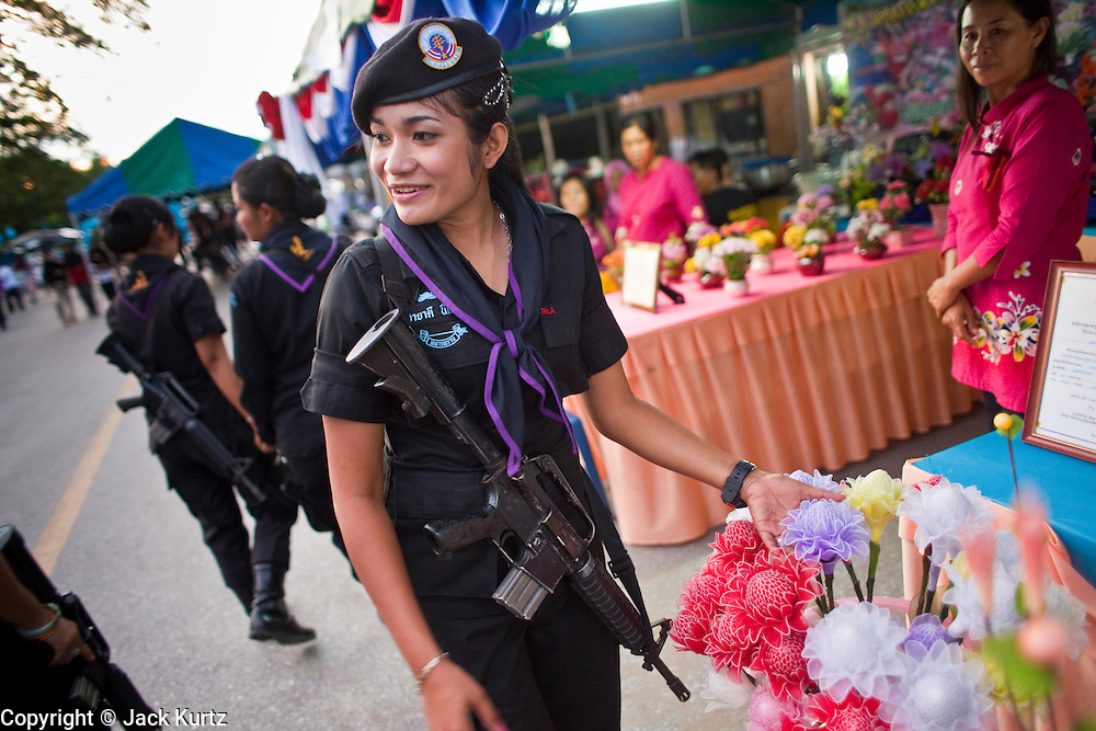 29 SEPTEMBER 2009 -- YARANG, PATTANI, THAILAND: Thai women Rangers, a paramilitary unit commanded by Thai Army officers, provide a security at a street fair in Yarang, Pattani, Thailand. The 39 women in the 44th Army Ranger Regiment are the only Thai women seeing front line active duty against Moslem insurgents in Thailand's deep south provinces of Pattani, Narathiwat and Yala. All of the other women serving in Thai security services are employed as office and clerical workers. The Ranger women are based at the Ranger camp in the Buddhist village of Baan Trokbon in Sai Buri district of Pattani province. The unit was formed in 2006 after Muslims complained about the way Thai soldiers, all men, treated Muslim women at roadblocks and during security sweeps. The women are frequently called upon to back up Thai regular army units when they are expected to encounter a large number of Muslim women. At least two of the women have been killed by Muslim insurgents. The unit has both Muslim and Buddhist members. Many of the women in the unit joined after either their fathers or husbands were killed by insurgents.   PHOTO BY JACK KURTZ
