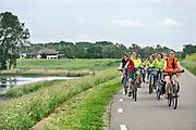 Nederland, Nijmegen, 5-6-2019 Een schoolklas fietst onder begeleiding van een leerkracht over de dijk in de ooijpolder. Ze hebben een excursie over de natuur in het riviereggebied gehad .Foto: Flip Franssen